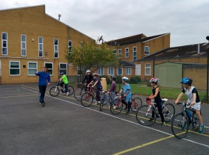 Children on bikes in a playground being coached